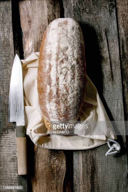 Whole grain fresh baked artisan rye-wheat organic bread from cotton textile bag, big knife over old wooden background. Flat lay, space.