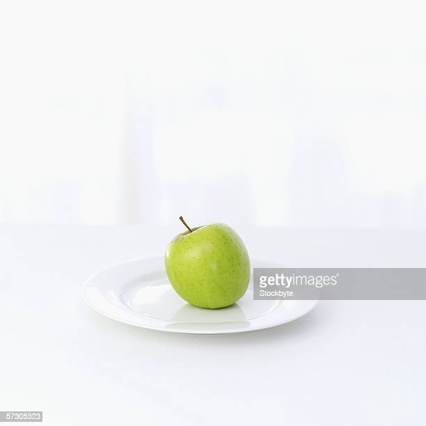 whole green apple on a plate