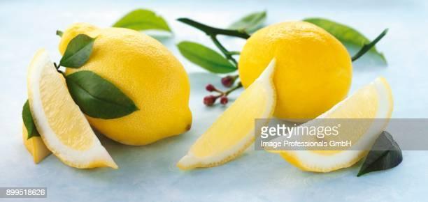whole lemons, lemon wedges and lemon leaves - lemon leaf stock photos and pictures