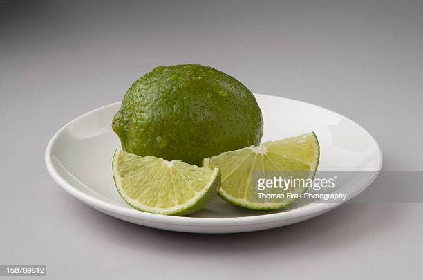 whole lime and 2 wedges -  firak stock pictures, royalty-free photos & images