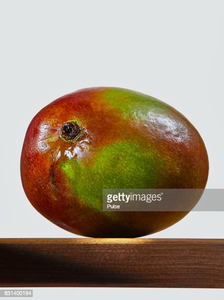 Whole mango on wooden surface