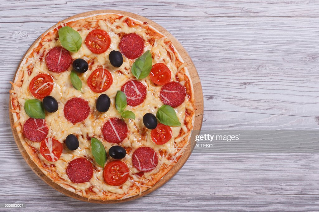 whole pizza with salami, tomato, cheese, olives and basil : Stock Photo