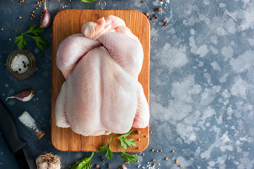 Whole raw chicken on a wooden board with spices for cooking, top view, horizontal, copy space 1042438074