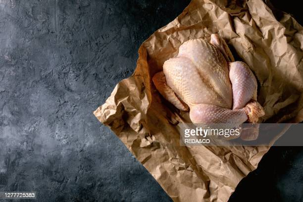 Whole raw organic uncooked farmer chicken poultry on crumpled craft paper over black concrete background. Flat lay. Space.