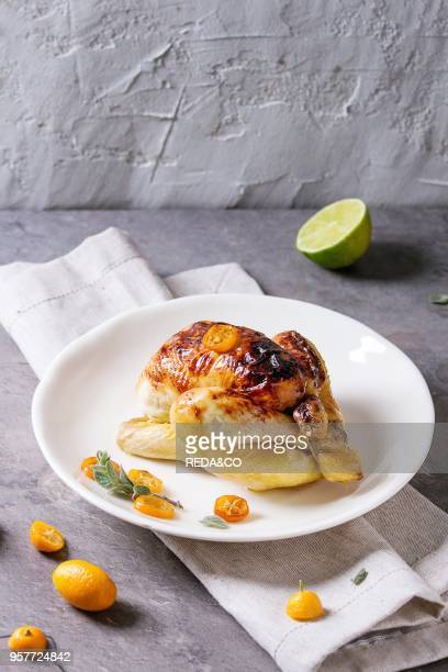 Whole roasted mini chicken cooking with caramelized kumquats served on white plate with textile napkin and fresh citrus fruits over gray kitchen...