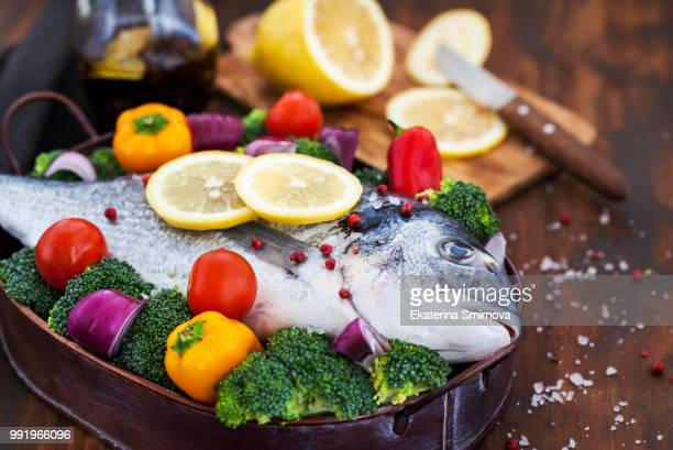 whole sea bream fish with vegetables - dorado fish stock photos and pictures