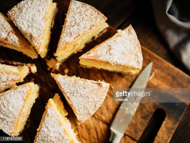 a whole victoria sponge cake from above sliced into rough portions against a dark wood chopping board. - sponge cake stock pictures, royalty-free photos & images