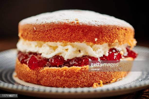 whole victoria sponge cake on a vintage palate. - sponge cake stock pictures, royalty-free photos & images
