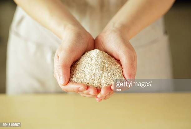 Whole wheat flour on palm of young woman,close up
