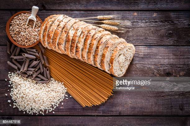 Wholegrain bread, pasta and rice on rustic wooden table