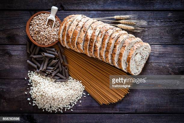 wholegrain bread, pasta and rice on rustic wooden table - wholegrain stock pictures, royalty-free photos & images
