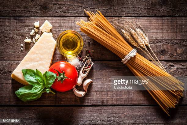 wholegrain spaghetti with ingredients on rustic wooden table - parmesan cheese stock pictures, royalty-free photos & images