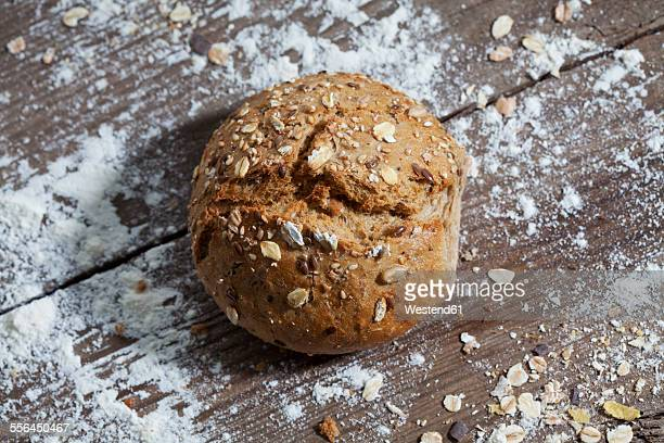 Wholemeal bread roll and flour on wood