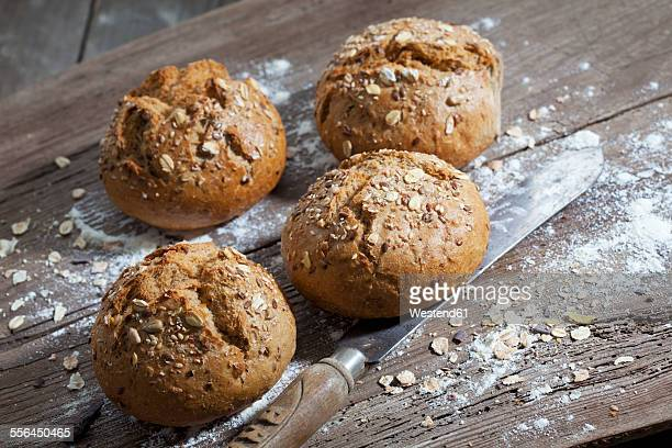 Wholemeal bread rolls, flour and old bread knife on wood
