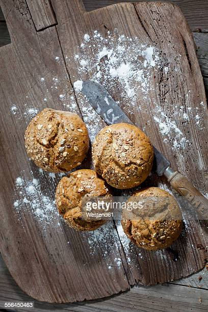 Wholemeal bread rolls, old bread knife and flour on wooden chopping board