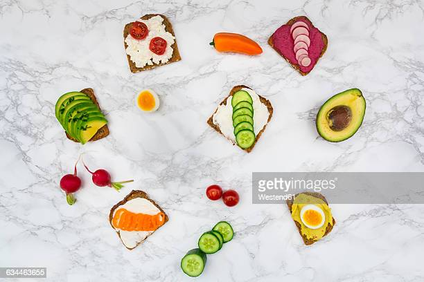 Wholemeal bread slices with different spreads and toppings on white marble