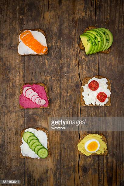 Wholemeal bread slices with different spreads and toppings on wood