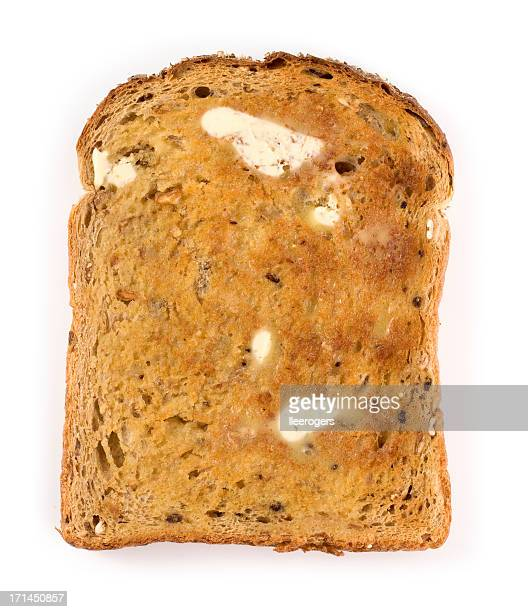 Wholemeal brown toast with butter on a white background