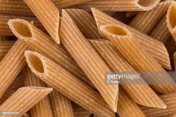 wholemeal pasta penne as close-up shot for background - wholegrain stock pictures, royalty-free photos & images
