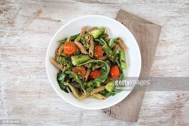 Wholemeal spelt rigatoni with green asparagus, cherry tomato and rocket pesto on plate