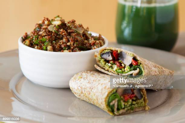 wholemeal wraps filled with portobello mushrooms, pesto, dried tomatoes and courgettes next to a bowl of quinoa with cabbage and coconut milk - ピストー ストックフォトと画像