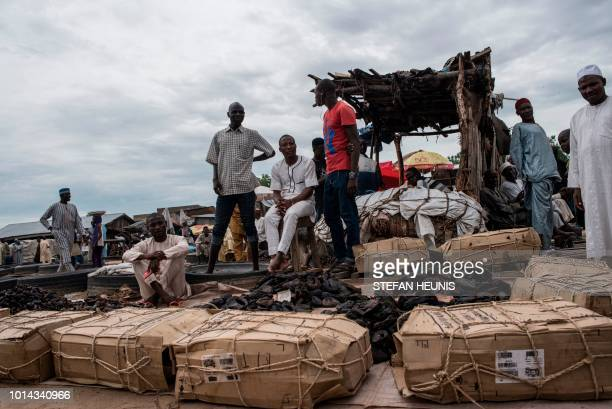 Wholesale fish merchants sit by their product waiting for customers at the Baga fish market in Maiduguri on July 31 2017 The fish trade in Borno...
