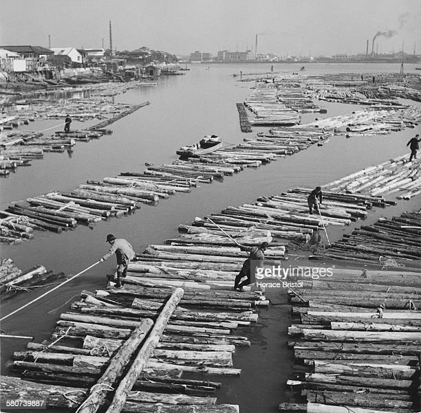 A wholesale lumber yard on the river in Fukagawa Tokyo Japan circa 1955