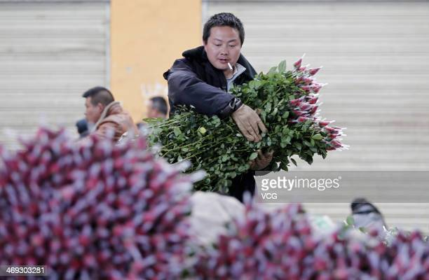 A wholesale vendor caries bouquets of roses at a flower market on February 13 2014 in Kunming China