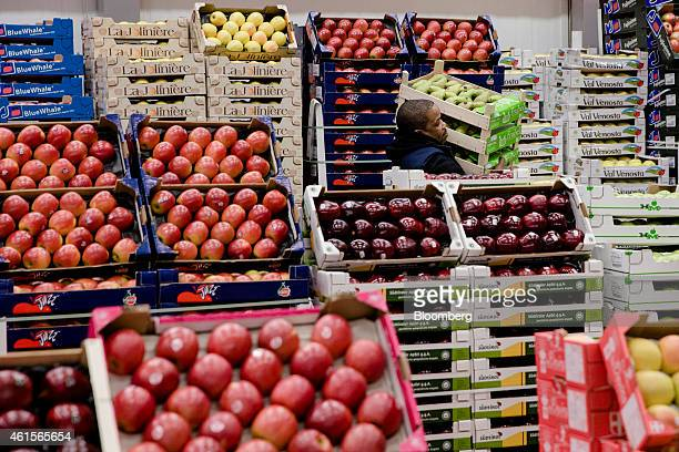 A wholesaler carries boxes of pears past crates of red apples in the fruit and vegetable area of Rungis wholesale food market in Rungis France on...