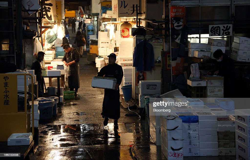A wholesaler, center, carries a box at Tsukiji Market in Tokyo, Japan, on Tuesday, April 9, 2013. After Bank of Japan Governor Haruhiko Kuroda's first policy meeting as governor on April 4, the central bank set a two-year horizon for the 2 percent annual price-increase target that it adopted in January at the urging of Prime Minister Shinzo Abe. Photographer: Tomohiro Ohsumi/Bloomberg via Getty Images