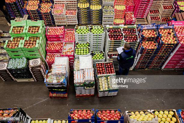 A wholesaler checks his inventory as he stands beside crates of red and green apples in the fruit and vegetable section of Rungis wholesale food...
