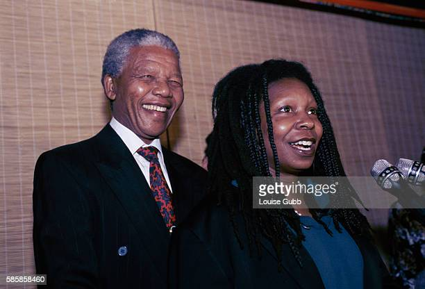 Whoopi Goldberg speaking into microphones while Nelson Mandela stands smiling behind her Former President of South Africa and longtime political...