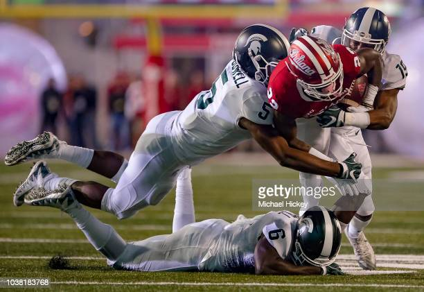 Whop Philyor of the Indiana Hoosiers is tackled while rushing by Andrew Dowell and Josh Butler of the Michigan State Spartans during the game at...