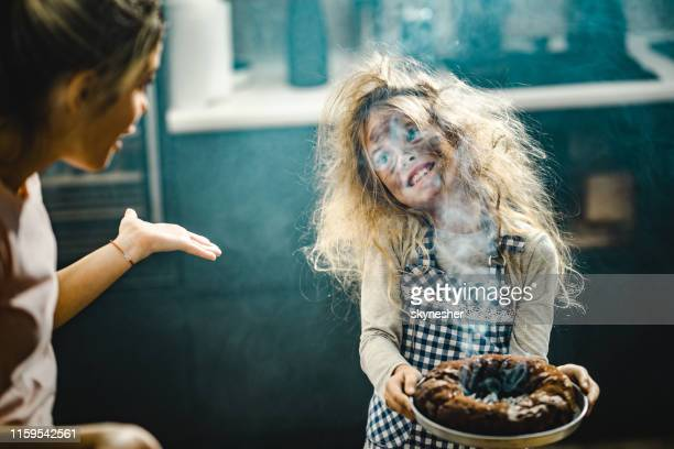 whops, the cake is a little bit burnt mommy! - imperfection stock pictures, royalty-free photos & images