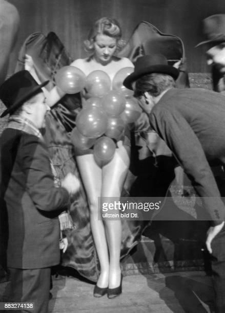 Während einer Probe in der Scala Berlin wird eine Darstellerin mit einer Zigarette von ihren am Körper hängenden Ballons befreit Hanns Hubmann...