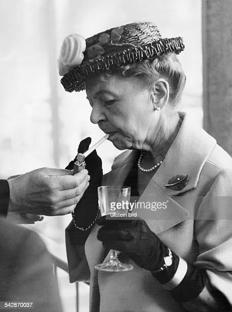 Während eines Empfangs wird Bonns ehemaliger Protokollchefin Erica Pappritz ein Feuerzeug zum Entzünden ihrer Zigarette gereicht Sie ist bekleidet...