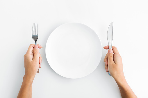 Whte plate with silver fork and knife on white background 1084491206