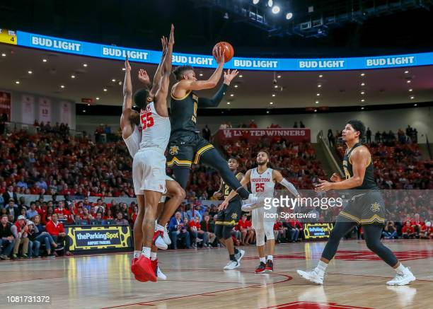 Wichita State Shockers guard Dexter Dennis leaps to pass the ball during the basketball game between the Wichita State Shockers and Houston Cougars...