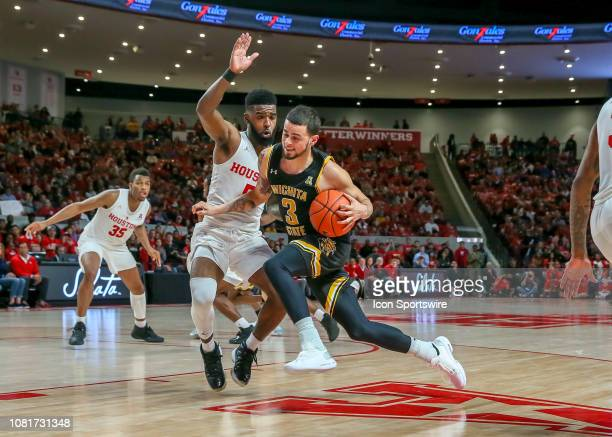 Wichita State Shockers guard Ricky Torres drives the ball past Houston Cougars guard Corey Davis Jr during the basketball game between the Wichita...