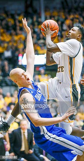 Wichita State's Zach Brown right drives to the basket against Drake's Jacon Enevold in the first half at Koch Arena in Wichita Kan on Thursday Dec 31...