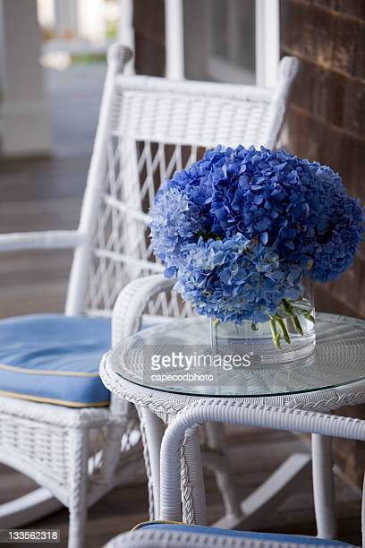 wicker and blue hydrangea  on a porch - wicker stock pictures, royalty-free photos & images