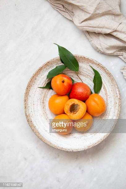 wicker basket apricot on a marble background with copy space and daylight - apricot stock pictures, royalty-free photos & images