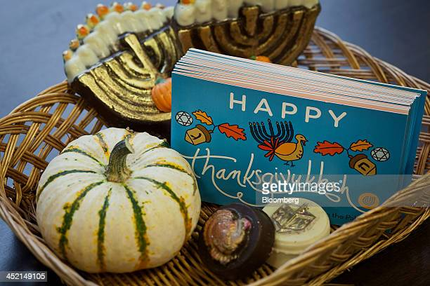 A wicker basket containing an assortment of chocolates decorated with both Hanukkah and Thanksgiving themes along with a stack of Thanksgivukkah...