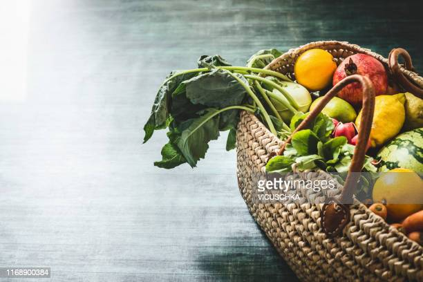 wicker basket with various organic vegetables and fruits from market - freshness fotografías e imágenes de stock