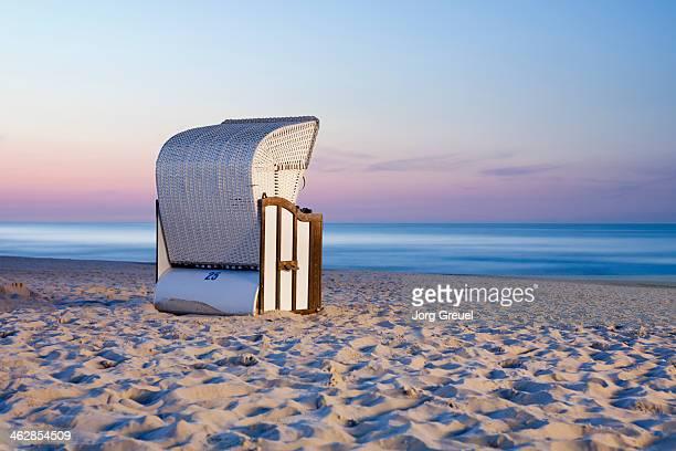 Wicker beach chair at dusk