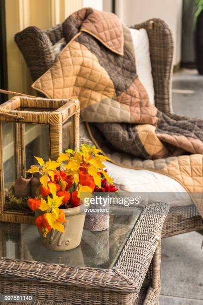 Wicker cozy armchair with blanket and small wicker glass table
