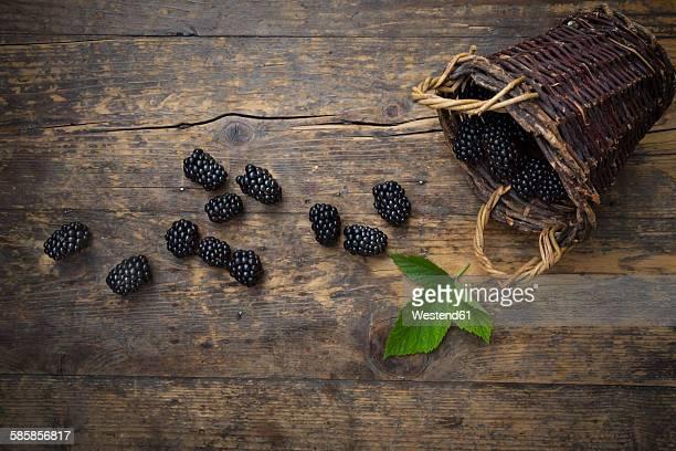 Wickerbasket. blackberries and a leaf on wood