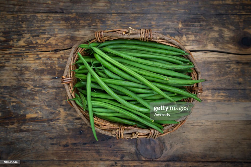 Wickerbasket of green beans on dark wood : Stock Photo