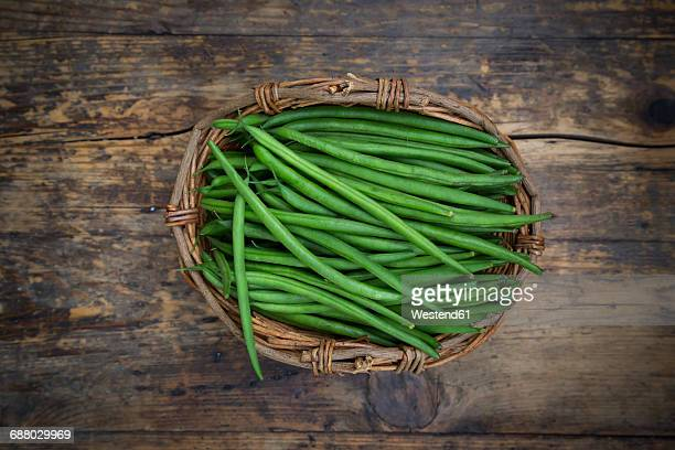 Wickerbasket of green beans on dark wood
