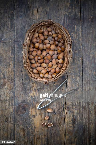 Wickerbasket of hazelnuts and nutcracker on dark wood
